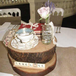 log slice centrepiece with china, old books & toilette water bottle